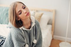 Young beautiful woman relaxing at home on the bed. Wearing funny grey hoodie. Waking up in lazy weekend morning Stock Photo