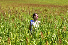 Young beautiful woman relaxing in the middle of a green cereals field during the last days of summer in the Pyrenees mountains Stock Photos