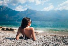 Young beautiful woman relaxing on pebble beach in beautiful Gard Stock Image