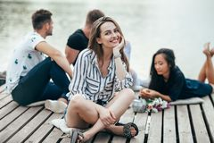 Young beautiful woman relaxing by river in company of friends stock photo