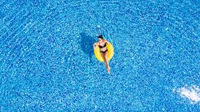 Young beautiful woman is relaxing in swimming pool with rubber yellow ring. royalty free stock images