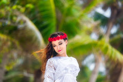 Young beautiful woman relaxing under the palm tree in a hotel on Stock Photo