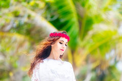 Young beautiful woman relaxing under the palm tree in a hotel on Royalty Free Stock Photography