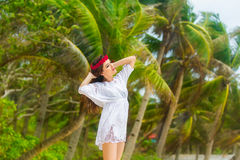Young beautiful woman relaxing under the palm tree in a hotel on Royalty Free Stock Photo