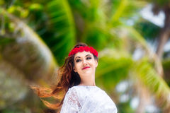 Young beautiful woman relaxing under the palm tree in a hotel on Stock Image