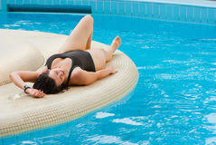 Young beautiful woman resting near pool. Young beautiful woman resting near swimming pool Stock Image