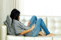 Young beautiful woman resting on a sofa with tablet computer Stock Photos