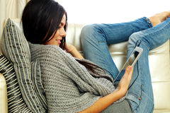 Young beautiful woman resting on a sofa with tablet computer Stock Images