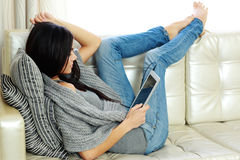 Young beautiful woman resting on a sofa with tablet computer Royalty Free Stock Photos