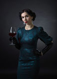 Young beautiful woman in retro style with red wine Royalty Free Stock Photography