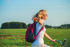 Young beautiful woman rides on a bicycle in the summertime on the green fields background and stretched out hand in the air.  stock photography