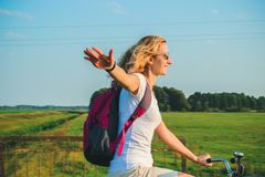Young beautiful woman rides on a bicycle in the summertime on the green fields background and stretched out hand in the air.  royalty free stock photos
