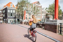 Woman with bicycle in Amsterdam city. Young beautiful woman riding a bicycle with bag and bouquet of tulips on the bridge over the water channel in Amsterdam old royalty free stock photography