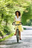 Young beautiful woman riding a bicycle in a park. Active people. Stock Photo