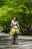 Young beautiful woman riding a bicycle in a park. Active people. Royalty Free Stock Photography