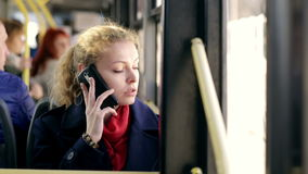 Young beautiful woman riding on the bus talking on the phone. In day stock video footage