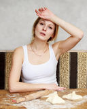 Young beautiful woman is rolling out the dough on the table, she Royalty Free Stock Photo