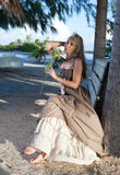 Young beautiful woman in a romantic dress on a bench on a beach, tropics Royalty Free Stock Images