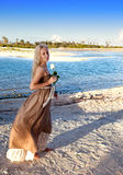 Young beautiful woman in a romantic dress with a rose on sand at the sea edge Stock Photo
