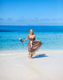 Young beautiful woman in a romantic dress with a rose on sand at the sea edge Stock Photos