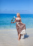 Young beautiful woman in a romantic dress with a rose on sand at the sea edge Stock Image