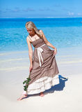 Young beautiful woman in a romantic dress with a rose on sand at the sea edge Stock Photography