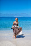 Young beautiful woman in a romantic dress with a rose on sand at the sea edge Royalty Free Stock Photo