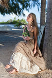The young beautiful woman in a romantic dress with a white rose in hands in an arbor on a beach. The young beautiful woman in a romantic dress in an arbor on a Royalty Free Stock Photo