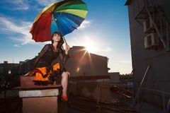 Young beautiful woman on the roof with an umbrella. Romantic wal. K model girls on the sky background Royalty Free Stock Photography