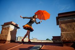 Young beautiful woman on the roof with an umbrella. Romantic wal. K model girls on the sky background Royalty Free Stock Image