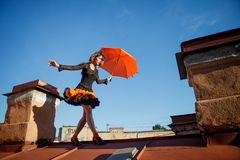 Young beautiful woman on the roof with an umbrella. Romantic wal. K model girls on the sky background Royalty Free Stock Photos