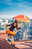 Young beautiful woman on the roof with an umbrella. Romantic wal. K model girls on the sky background Stock Images