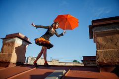 Young beautiful woman on the roof with an umbrella. Romantic wal. K model girls on the sky background Stock Photo