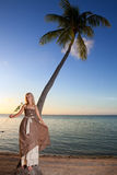 Young beautiful woman with a rose on a palm tree on seacoast. Stock Image