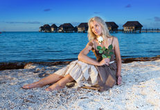The young beautiful woman with a rose sits on sand at the sea edge Royalty Free Stock Images