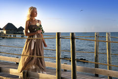 The young beautiful woman with a rose on a wooden path at the sea, tropics Stock Photos
