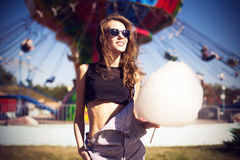 Young beautiful woman in round hipster sunglasses and with long. Curly hair smiling and posing in lunapark with candy floss Royalty Free Stock Image