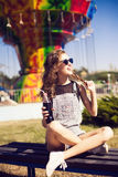 Young beautiful woman in round hipster sunglasses and with long. Curly hair smiling and posing in lunapark. Soft warm colours Stock Image