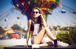 Young beautiful woman in round hipster sunglasses and with long. Curly hair smiling and posing in lunapark.  Soft warm colours Stock Photography