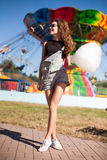 Young beautiful woman in round hipster sunglasses and with long. Curly hair smiling and posing in lunapark.  Soft warm colours Stock Photo