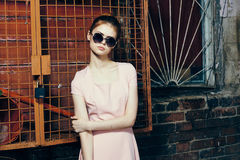 Young beautiful woman in round sunglasses on the street stock photo