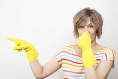 Young beautiful woman in rubber gloves holding her nose. Pretty blonde woman in rubber gloves holding her nose with her hand showing on to something Stock Images