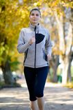 Young Beautiful Woman Running in the Autumn Park Stock Images