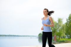 Young Beautiful Woman Running on the Beach Trail in the Morning Stock Photos