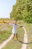 Young beautiful woman running in grass barefoot and holding shoes in hands Stock Images