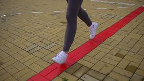 Young beautiful woman is running in the park. Close up of running shoes and legs in action. slow-motion stock video
