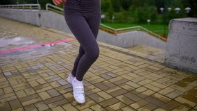 Young beautiful woman is running in the park. Close up of running shoes and legs in action. slow-motion stock footage