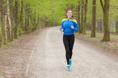 Young beautiful woman running on a trail Stock Images