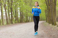 Young beautiful woman running on a trail Royalty Free Stock Photography