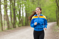 Young beautiful woman running on a trail Stock Photos